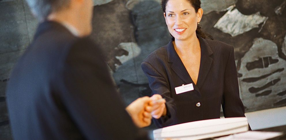 PHOTO: Hotel receptionist smiles at guest