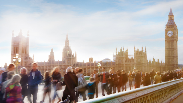 Tourists cross the River Thames on a foot bridge, in London, in this file photo.