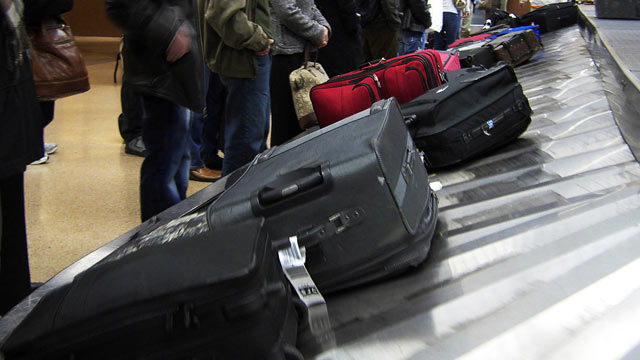 PHOTO: Passengers wait for luggage on a baggage carousel at San Jose International Airport in San Jose, Calif.
