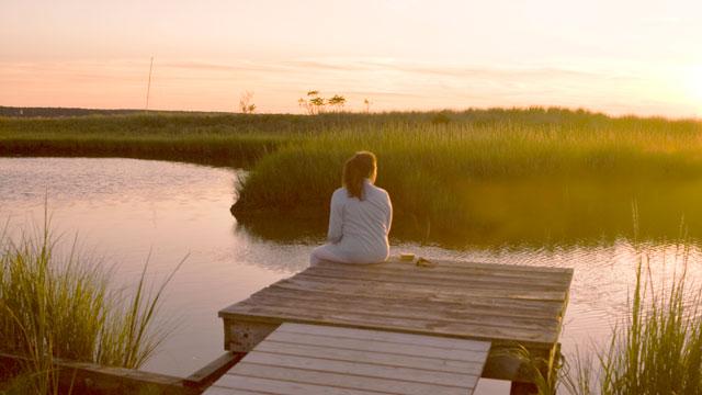 PHOTO: Woman is seen sitting on dock overlooking marsh, Sag Harbor, NY.