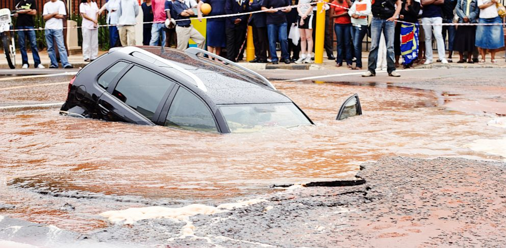 PHOTO: Behind police cordon tape, a car slides into muddy sinkhole in this undated stock photo.