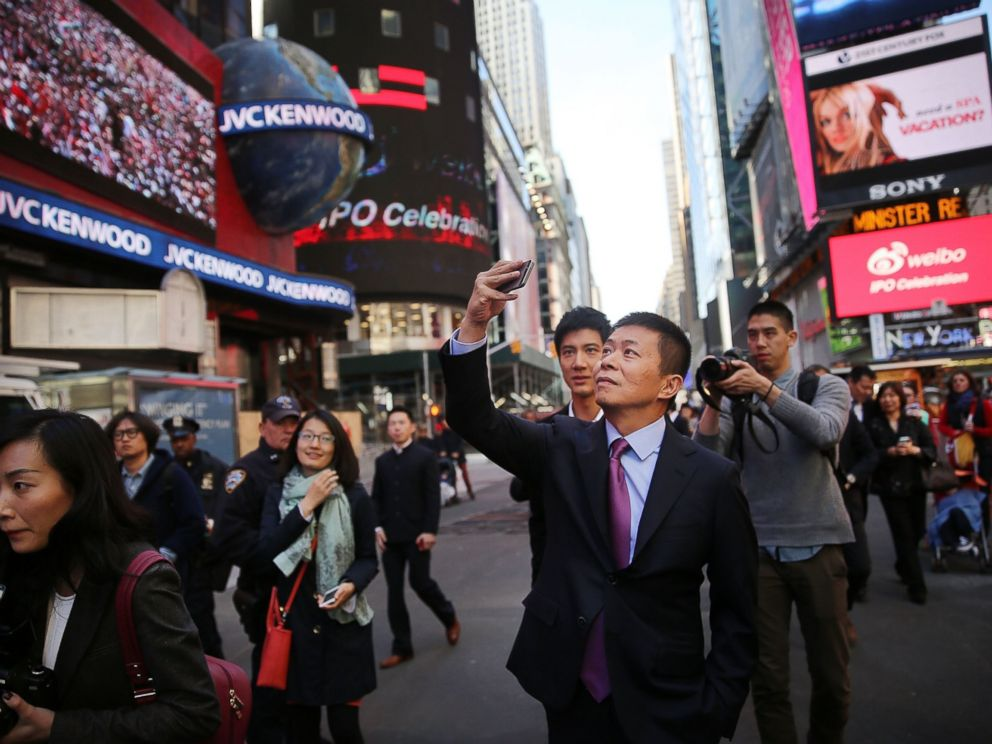 PHOTO: Chinas Weibo CEO Charles Chao takes a cell phone picture in Times Square moments after Weibo began trading on the Nasdaq exchange, April 17, 2014 in New York City.