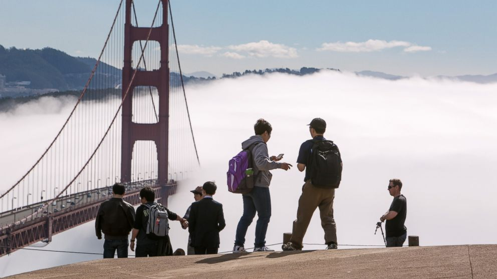 A group of tourists take photographs at the Golden Gate Bridge on Feb. 13, 2014, in San Francisco, Calif.