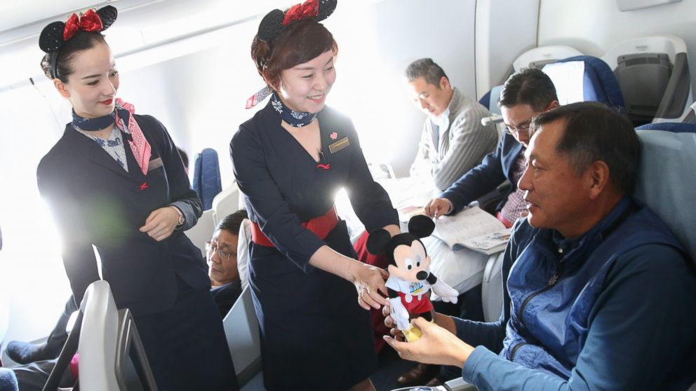 Crew members from China Eastern Airlines present Disney souvenirs to passengers on a Disney-themed plane flying from Shanghai to Beijing, April 26, 2016.