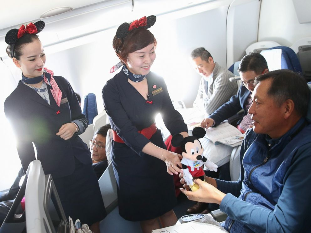 PHOTO: Crew members from China Eastern Airlines present Disney souvenirs to passengers on a Disney-themed plane flying from Shanghai to Beijing, April 26, 2016.