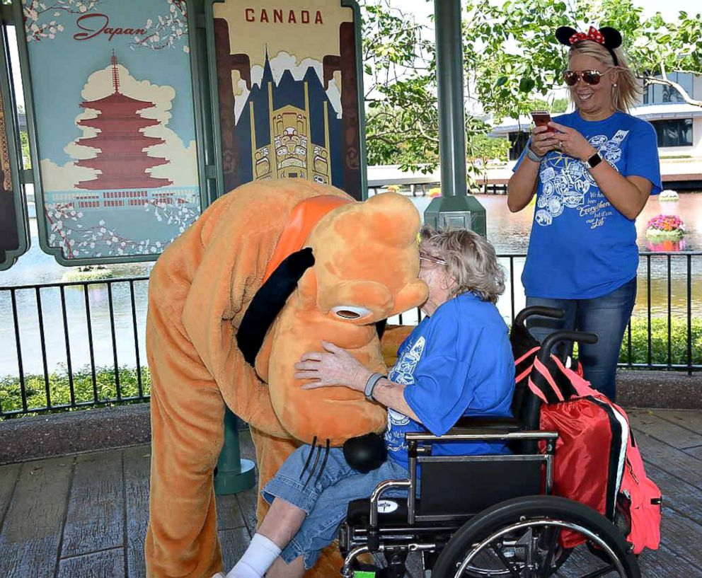 A nursing home resident meets the Disney character, Pluto, while vacationing in Disney's Magic Kingdom in April 2018.