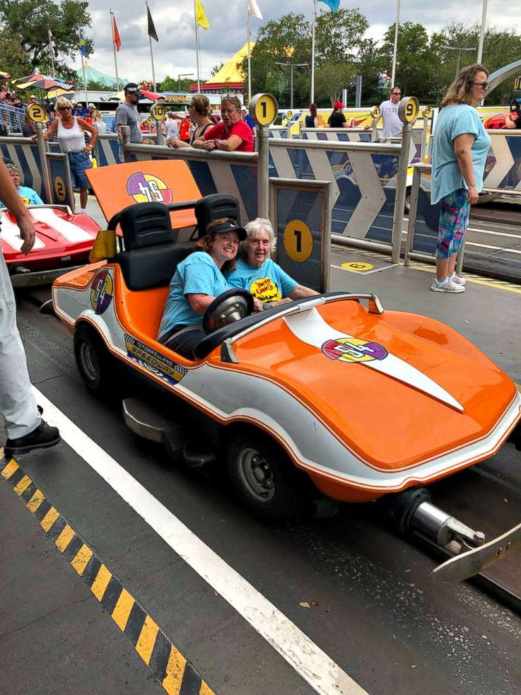 A nursing home resident and employee of Signature HealthCARE enjoy a ride at Disney World in Florida in April 2018.
