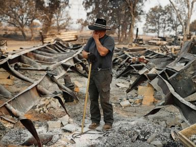 PHOTO: Ed Bledsoe tries to hold back tears as he searches through what remains of his home, Aug. 13, 2018, following the Carr Fire in Redding, Calif.