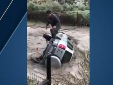 WATCH:  Driver rescued after car is swept up by floodwaters
