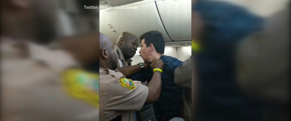 VIDEO: A flight from Miami to Chicago was delayed for over an hour after one passenger was forcibly removed by police following a fight with another passenger.