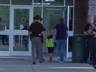 WATCH: Boy gets police escort to school after officer dad's death