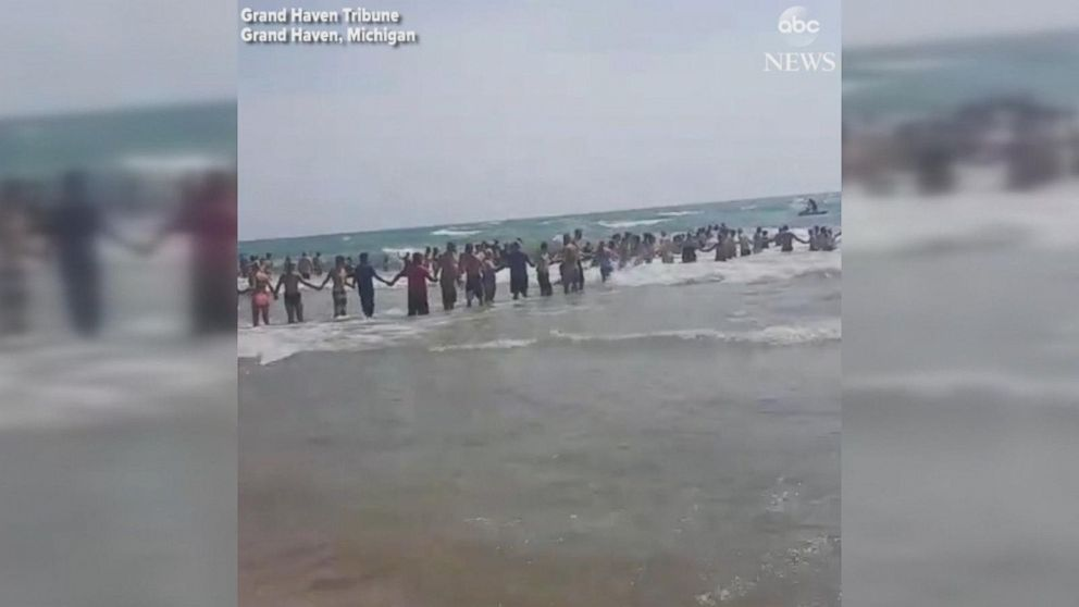 Beachgoers form human chain in attempt to rescue swimmers
