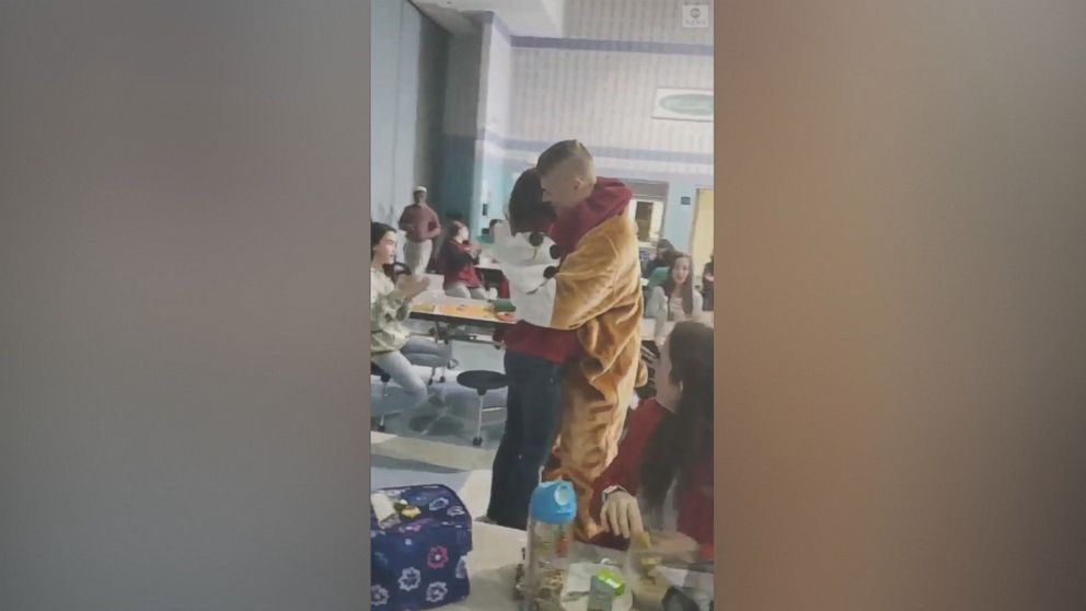 VIDEO: Students are stunned when the school's mascot walking through the cafeteria turned out to be a Coast Guard sergeant surprising his daughter.