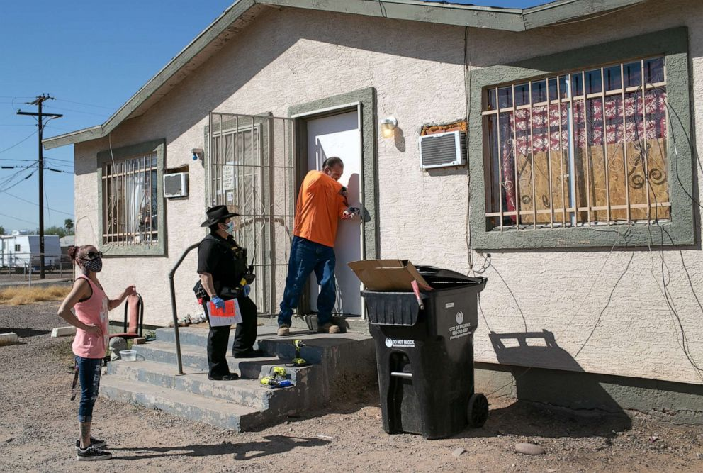 PHOTO: A maintenance man breaks the lock of a house as Maricopa County constable Darlene Martinez serves an eviction order on Oct. 1, 2020, in Phoenix.