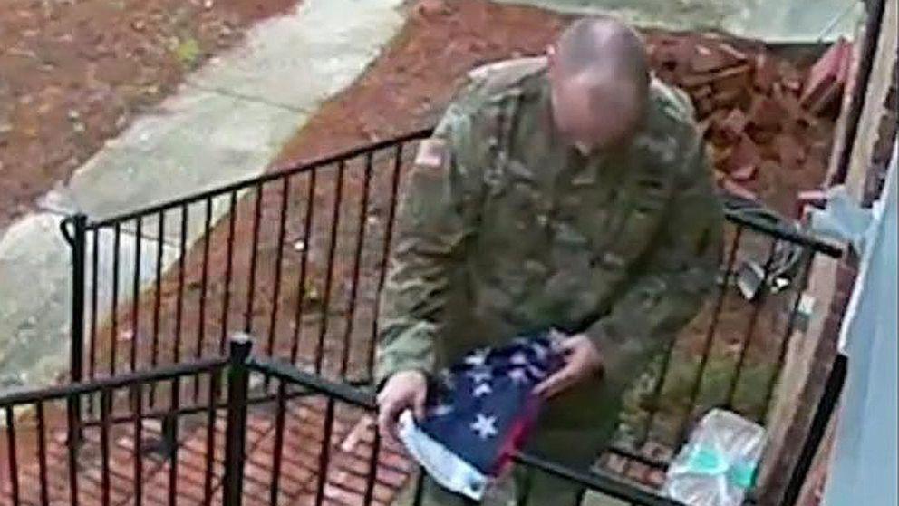 Man in military garb folds neighbor's American flag