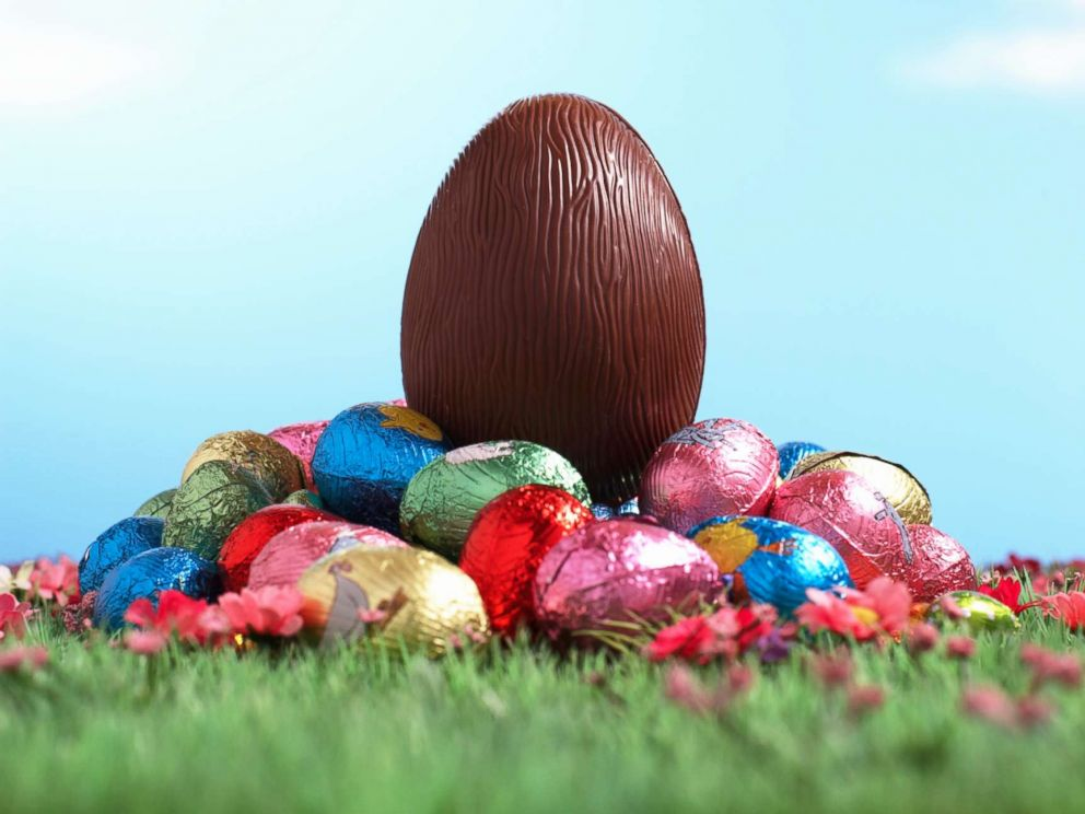 PHOTO: A chocolate egg sits on pile of foil wrapped Easter eggs on grass.