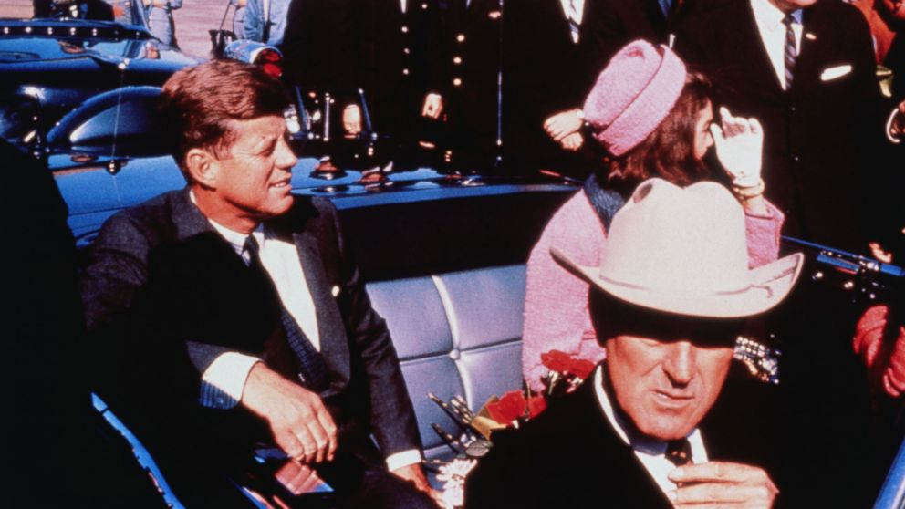 Texas Governor John Connally adjusts his tie (foreground) as President .John Kennedy and wife Jackie, in a pink outfit, settled in rear seats, prepared for motorcade into city from airport, Nov. 22 1963.