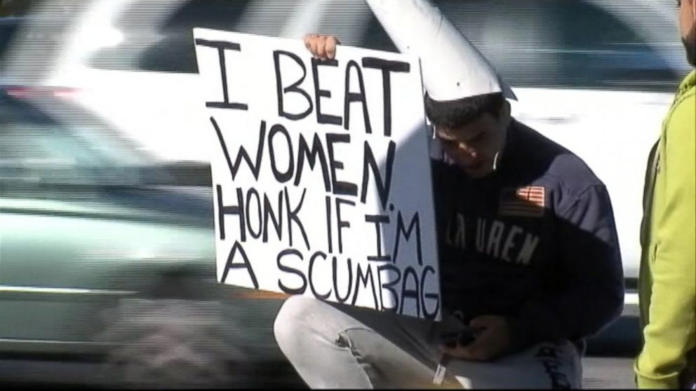 """A Tampa, Fla. woman chooses to embarrass her alleged attacker by having him hold a sign that says """"I beat women. Honk if I'm a scumbag."""""""