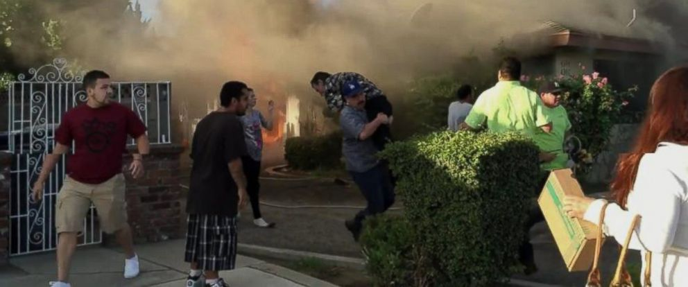 PHOTO: This cellphone video of a house on fire in Fresno, Calif., shows an unidentified man calmly walking toward the house and entering through the flames. Moments later he walks out with a man over his shoulder.