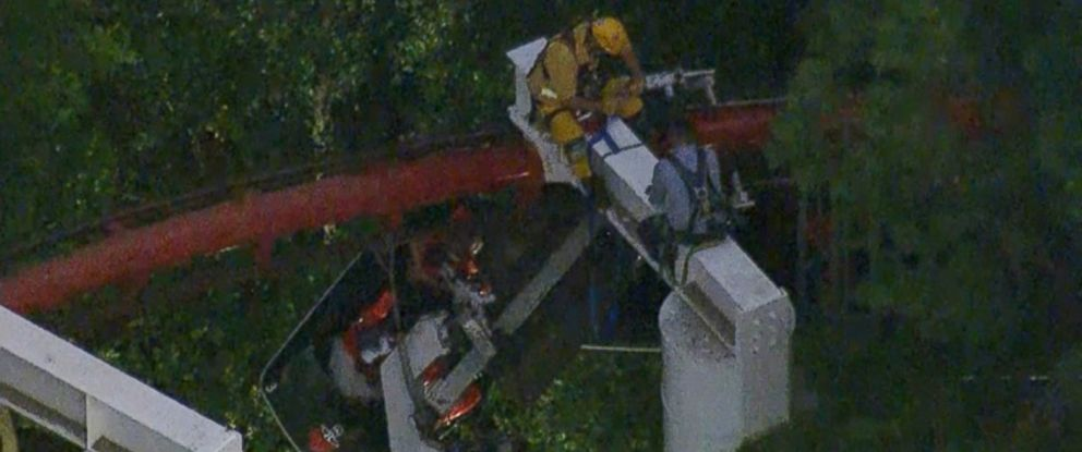 PHOTO: Riders wait patiently as firefighters try to reach them through a tangle of track and trees, July 7, 2014.