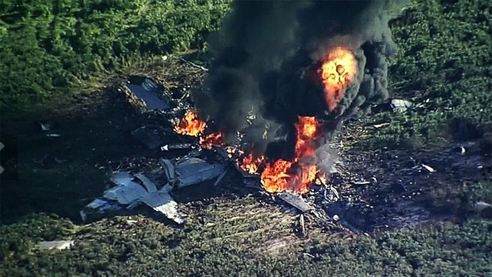 Smoke and flames rise from a military plane that crashed in a farm field, in Itta Bena, Miss., killing several.