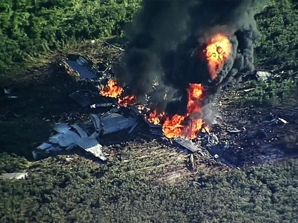PHOTO: Smoke and flames rise from a military plane that crashed in a farm field, in Itta Bena, Miss., killing several.