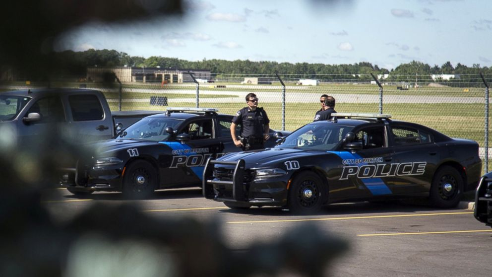 Burton Police Officers gather at Bishop International Airport, June 21, 2017, in Flint, Mich. Officials evacuated the airport Wednesday, where a witness said he saw an officer bleeding from his neck and a knife nearby on the ground.