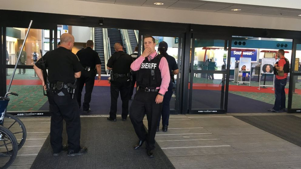 Police officers gather at a terminal at Bishop International Airport, June 21, 2017, in Flint, Mich. Officials evacuated the airport, where a witness said he saw an officer bleeding from his neck and a knife nearby on the ground.  On Twitter, Michigan State Police say the officer is in critical condition and the FBI was leading the investigation.