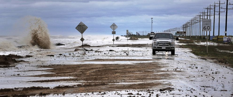 PHOTO: Vehicles navigate past waves and debris washing over State Highway 87 as Tropical Storm Cindy approaches, June 21, 2017, in High Island, Texas.