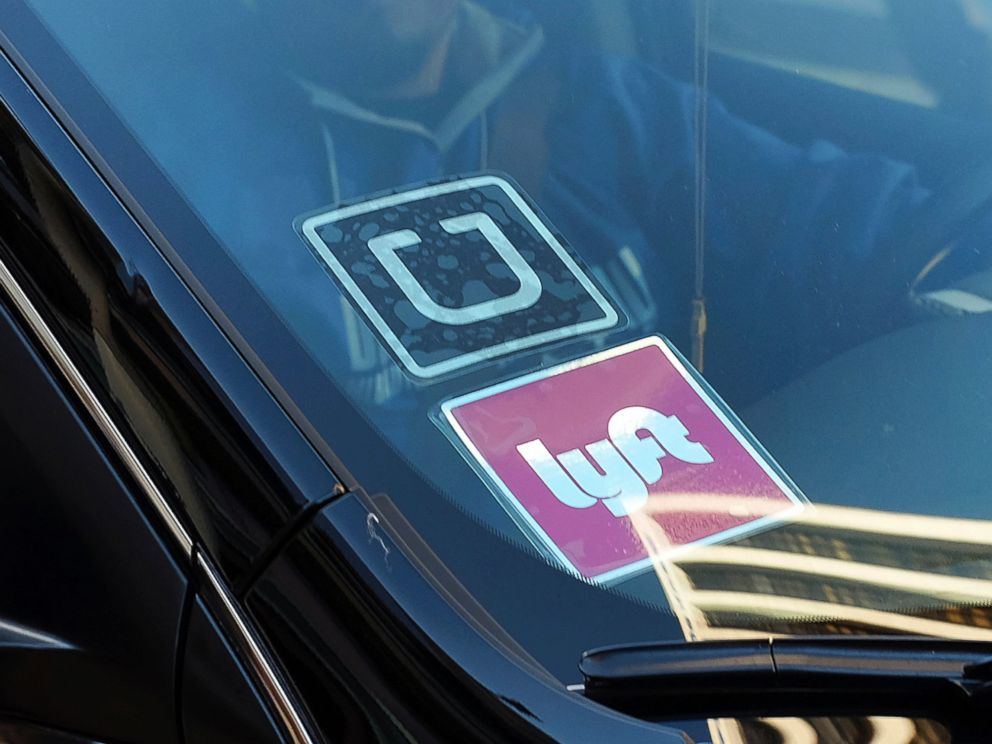 PHOTO: A driver displaying Lyft and Uber stickers on his front windshield, drops off a customer in downtown Los Angeles, Jan. 12, 2016.