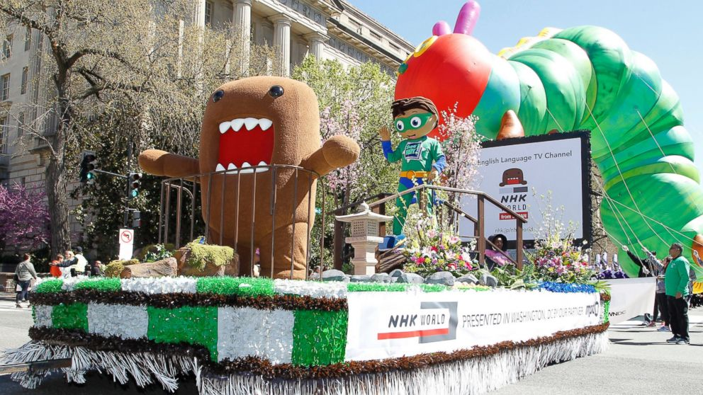 NHK WORLD TV's mascot Domo, left, and PBS Kids animated TV series character, Super Why!, right, on NHK WORLD TV's float during The National Cherry Blossom Festival Parade, April 8, 2017 in Washington.
