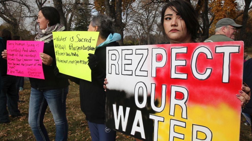 Holly Doll, of Mandan, an enrolled member of the Standing Rock Sioux Tribe, holds a protest sign outside the state's capitol building in Bismarck, N.D., Oct. 29, 2016.