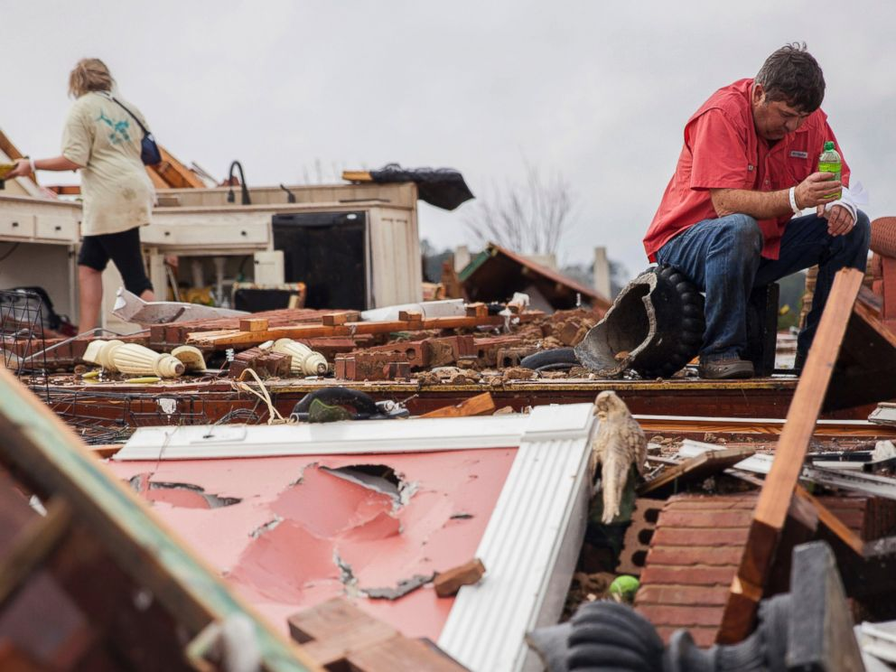 PHOTO: Jeff Bullard sits in what used to be the foyer of his home as his daughter, Jenny Bullard, looks through debris at their home that was damaged by a tornado, Jan. 22, 2017, in Adel, Georgia.