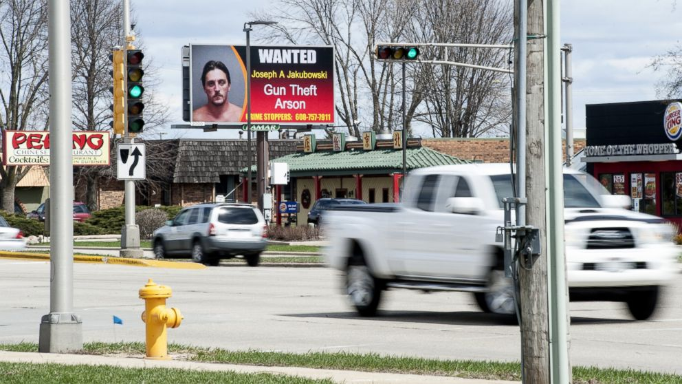 In this Thursday, April 6, 2017 photo, vehicles drive by an electronic billboard in Janesville, Wis., showing a wanted sign for Joseph Jakubowski.