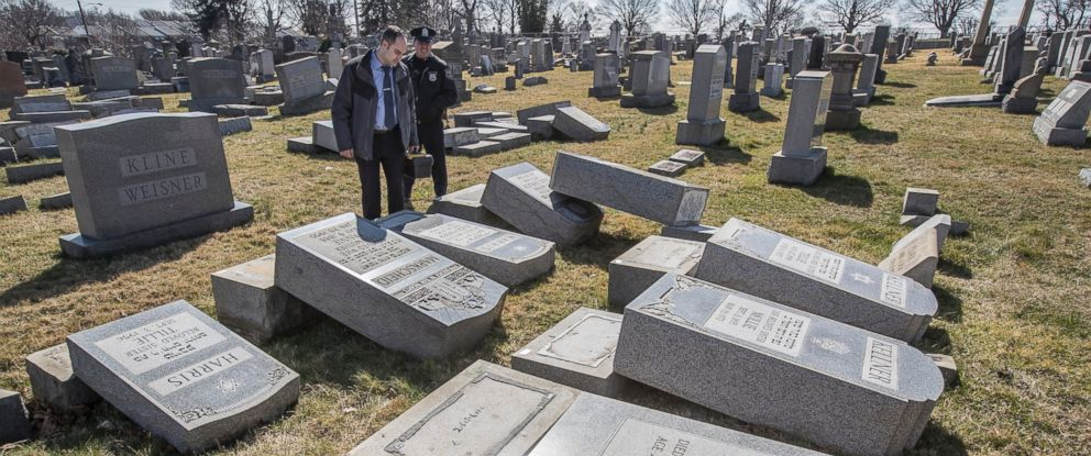 PHOTO: Northeast Philadelphia Police Det. Timothy McIntyre and another Philadelphia police officer look over tombstones that were vandalized in the Jewish Mount Carmel Cemetery, Feb. 26, 2017 in Philadelphia.