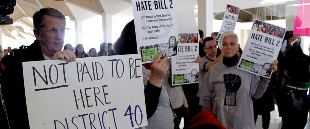 PHOTO: Opponents of HB2 hold signs outside the North Carolina House chambers gallery as the North Carolina General Assembly convenes for a special session at the Legislative Building in Raleigh, North Carolina, Dec. 21, 2016.