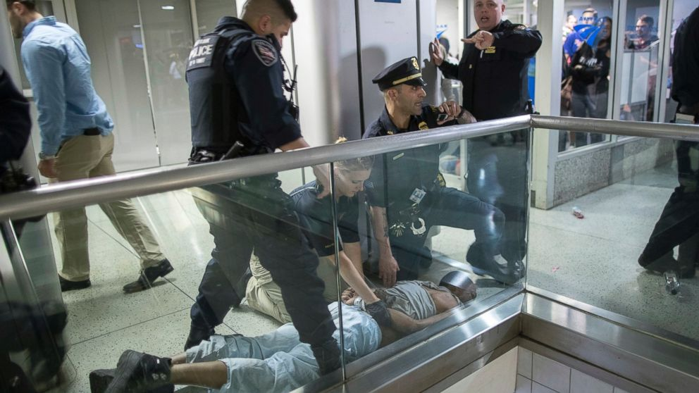 New York City police officers detain a passenger from a disabled New Jersey Transit train who became belligerent and sparked a stampede among passengers leaving the overcrowded station once the train finally arrived at New York's Penn Station, April 14, 2017.