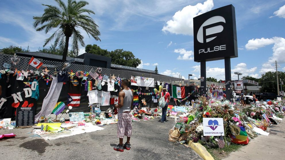 In this July 11, 2016, file photo, visitors at a makeshift memorial outside the Pulse nightclub, the day before the one month anniversary of the mass shooting, in Orlando, Fla.