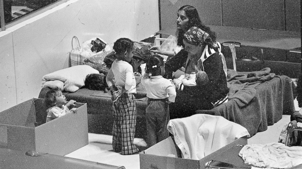 Kathy Moody uses a cardboard box for a playpen for her daughter while they wait in the evacuation center at Hershey sports arena for radiation from the Three Mile Island nuclear power plant to stop, March 31, 1979.