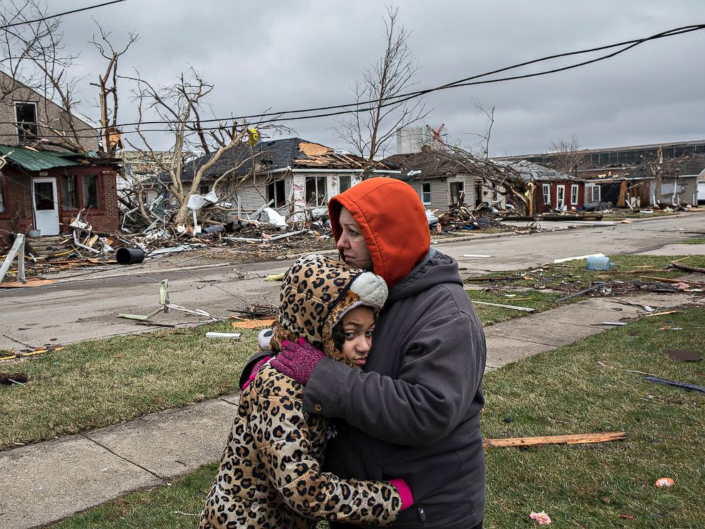 PHOTO: Valerie McAvoy and daughter Jayda Weathersby, 9, hug as they survey the tornado damage to their neighborhood, March 1, 2017, in Naplate, Ill.