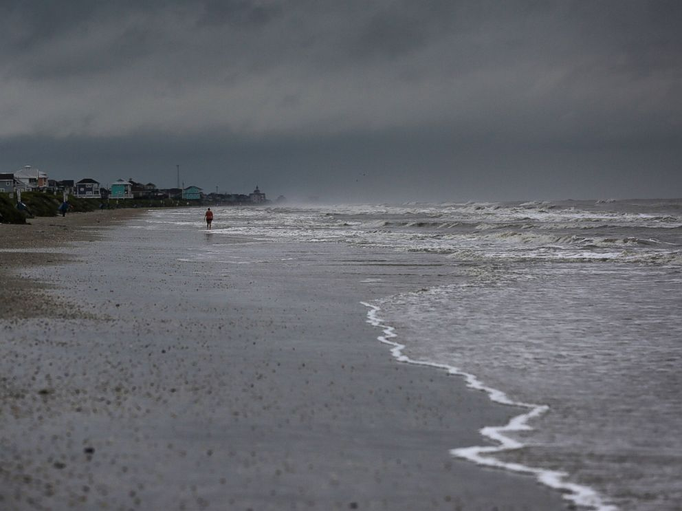 PHOTO: A woman walks along the beach the morning after Tropical Storm Cindy made landfall, June 22, 2017, on the Bolivar Peninsula, Texas.