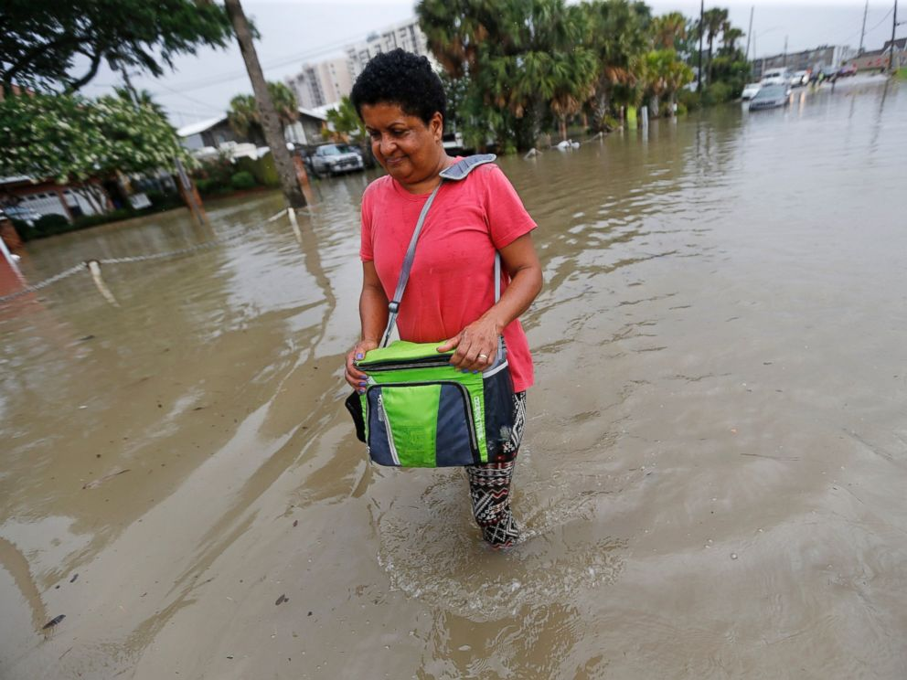 PHOTO: Esther Martens walk through a flooded roadway to get to her car in the West End section of New Orleans, June 21, 2017.