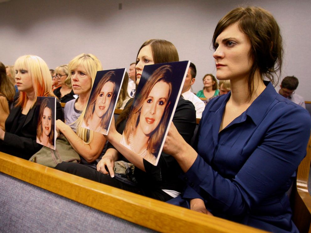 PHOTO: Family members hold up photos of Michele MacNeill facing Martin MacNeill as he enters the courtroom in Provo, Utah, Aug. 27, 2012.