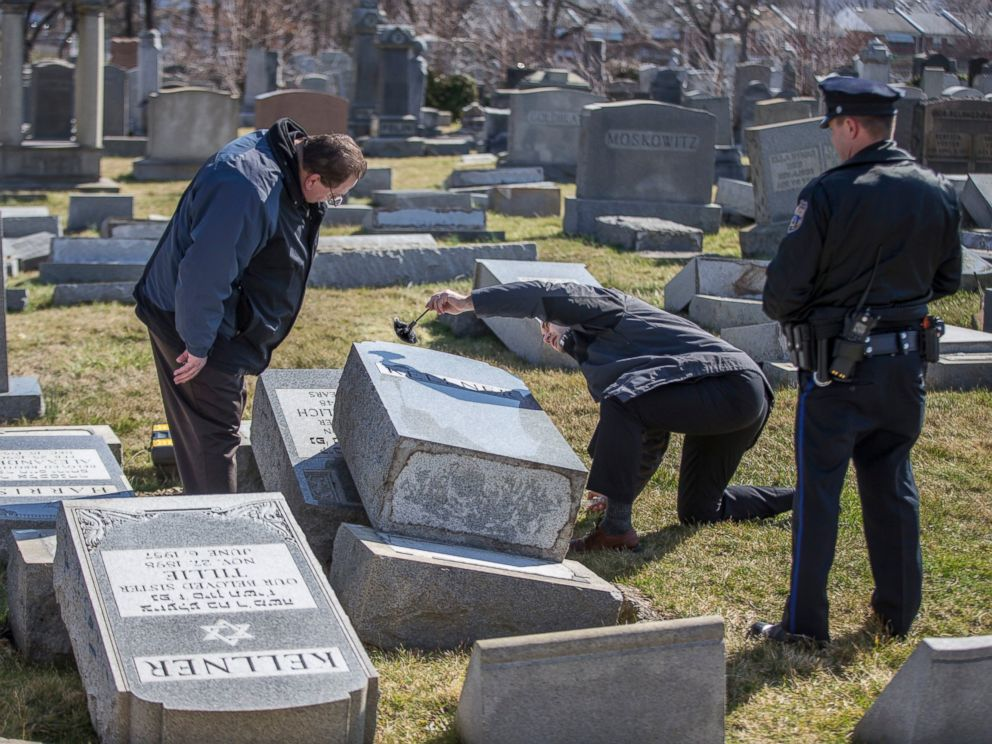 PHOTO: Northeast Philadelphia Police Detective Timothy McIntyre, center, dusts for fingerprints one of the headstones that were knocked down as Detective Nick McReynolds, left, looks on at Mount Carmel Cemetery in Philadelphia, Feb. 26, 2017.