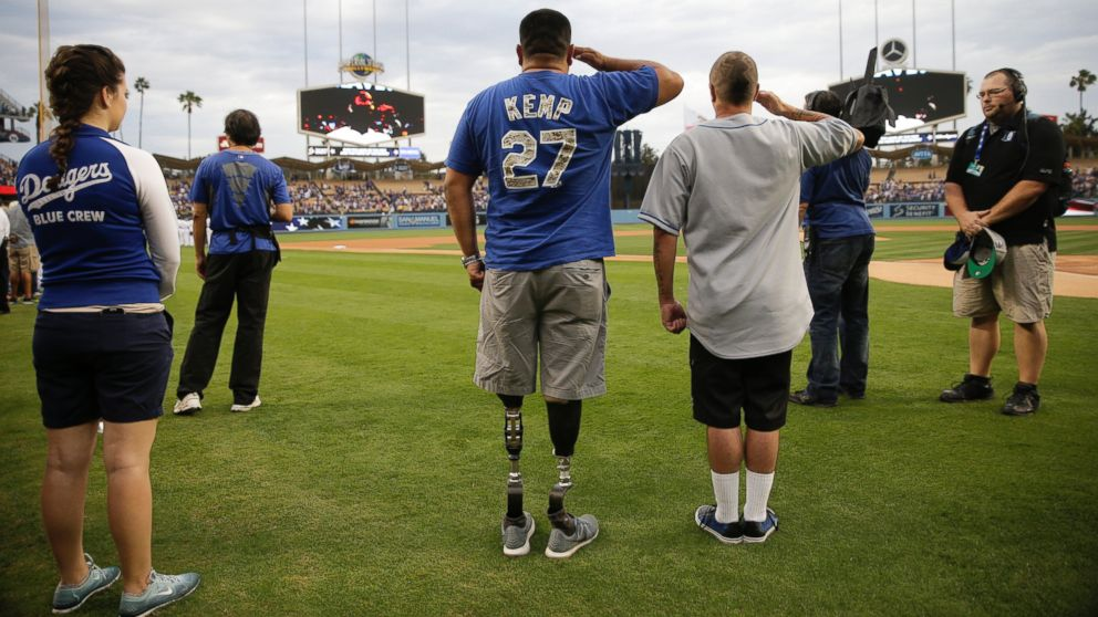 U.S. Army veteran Wesley Barrientos, center, who lost his legs in 2007 while serving in Iraq, listens to the national anthem before a baseball game between the Los Angeles Dodgers and the Arizona Diamondbacks, June 9, 2015, in Los Angeles.