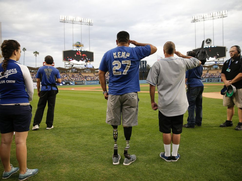 PHOTO: U.S. Army veteran Wesley Barrientos, center, who lost his legs in 2007 while serving in Iraq, listens to the national anthem before a baseball game between the Los Angeles Dodgers and the Arizona Diamondbacks, June 9, 2015, in Los Angeles.