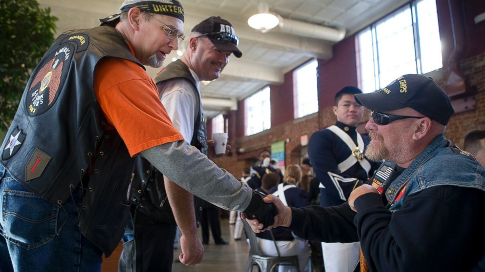 Joel Funk, of Salem, left, and Steve Lovelace, of Botetourt, center, both with the American Legion Riders, greet Vietnam War veteran Charles Shull of Roanoke prior to Virginia's Veterans Parade, Nov. 5, 2016, during a meet and greet at the City Market building in Roanoke, Virginia.