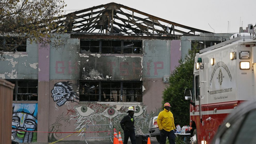 A pair of Oakland fire officials walk past the remains of the Ghost Ship warehouse fire, Dec. 7, 2016, in Oakland, California.