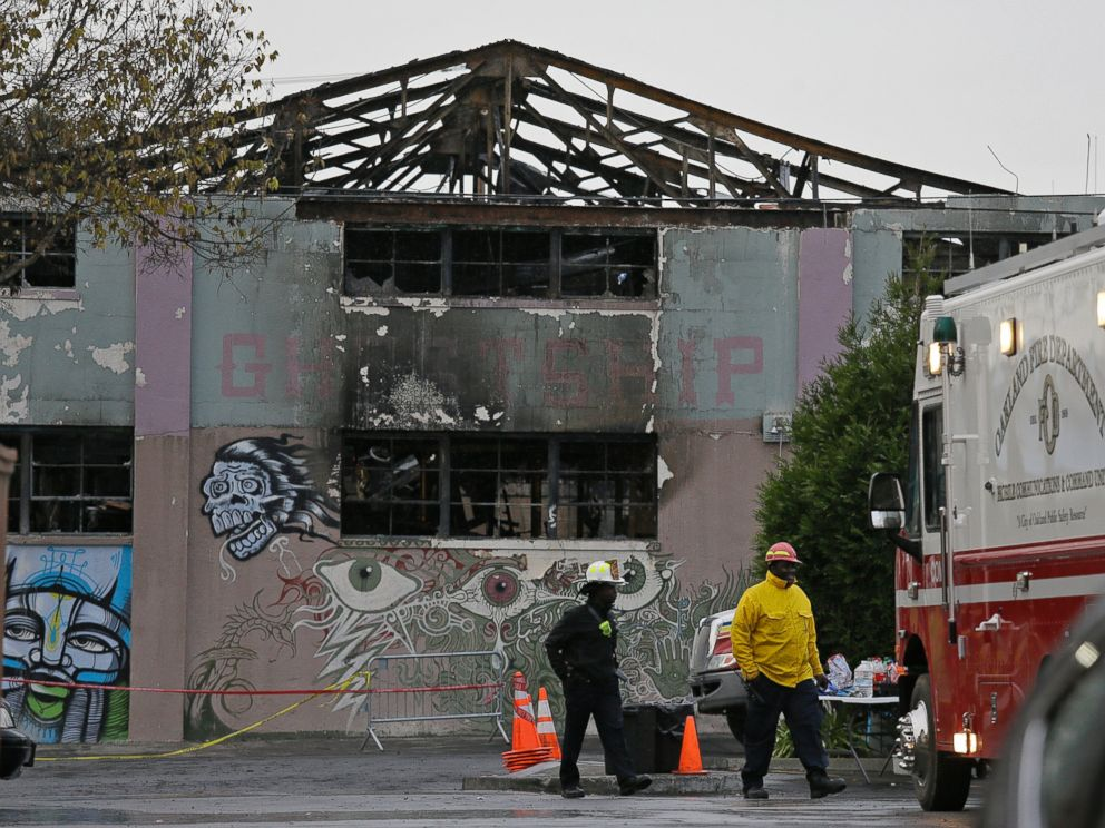 PHOTO: A pair of Oakland fire officials walk past the remains of the Ghost Ship warehouse fire, Dec. 7, 2016, in Oakland, California.