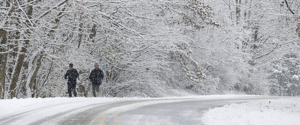PHOTO: Ken Perry and Stan Ly go for a run in Eagle Creek Park as snow falls, Dec. 13, 2016, in Indianapolis.